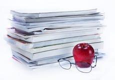Zeitschriften- und Buchstapel mit Gläsern und Apfel Stockbild