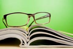 Zeitschriften und Gläser, die auf Tabelle liegen Stockfoto