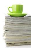 Zeitschriften und Kaffeetasse stockfoto
