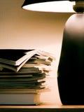 Zeitschriften unter Abendlampenleuchte Lizenzfreies Stockbild