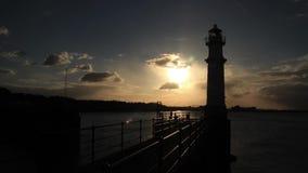 Zeitspanne der Sonne, die unten hinter einen Leuchtturm geht stock video footage
