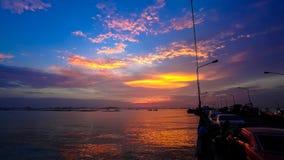Zeitspanne des drastischen Sonnenunterganghimmels in Meer mit Hafenschattenbildvordergrund stock video