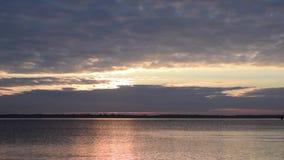Zeitspanne mit dem aufgehende Sonne, das durch Wolken über See scheint stock video