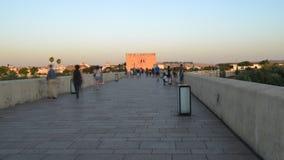 Zeitspanne von den Touristen, welche die berühmte römische Brücke von Cordoba, Spanien über Guadalquivir-Fluss kreuzen stock video