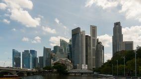 Zeitspanne von Wolken und von blauem Himmel über im Stadtzentrum gelegenem Finanzzentrum und von Fähren entlang Singapur-Fluss stock footage