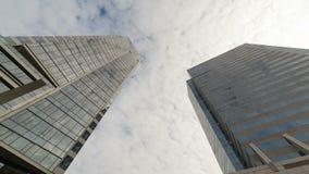 Zeitspannefilm UHD 4k von weißen beweglichen Wolken über hohen Glasturmgebäuden der im Stadtzentrum gelegenen Stadt mit Reflexion stock video
