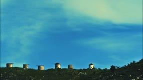 Zeitspanneschuß der verlassenen Mühlen an der Spitze der Hügel an einem bewölkten Tag mit einem blauen Himmel stock video