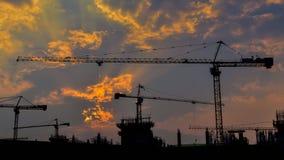 Zeitspannesonnenuntergang und Schattenbildkran, der in der großen Baustelle arbeitet (summen Sie herein) laut stock video
