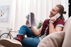 Zeitung des gutaussehenden Mannes Leseund Unterhaltung auf Smartphone Lizenzfreie Stockfotografie