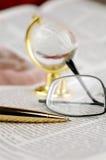 Zeitung, Feder, Gläser und Kugel Lizenzfreie Stockfotos