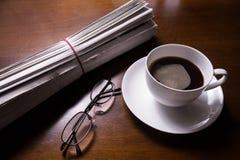 Zeitung, Gläser und Schale auf Schreibtisch Stockbilder