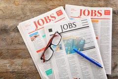 Zeitungen mit Schlagzeilen JOBS und Gläser auf hölzernem Hintergrund stockfotos