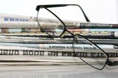 Zeitungen und Gläser stockfoto