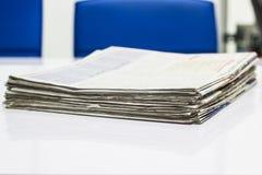 Zeitungs-Stapel auf weißer Tabelle Stockfotografie