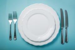 Zeitweiliges fastin Konzept - leere Platte auf blauem Hintergrund Stockfoto