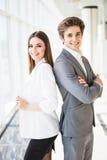 Zeker commercieel team van mens en vrouw die zich met gekruiste handen de bevinden paar van succes bedrijfsmensen klaar te handel Stock Afbeelding