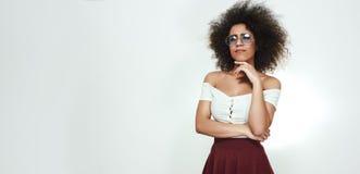 Zeker en slim Brede foto van aantrekkelijke afro Amerikaanse vrouw in modieuze eyewear en sexy kleren wat betreft haar kin royalty-vrije stock afbeelding