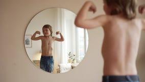 Zeker jong geitje die zijn spieren in spiegel bekijken veronderstellen die dat hij super held is stock videobeelden