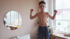 Zeker jong geitje die zijn spieren in spiegel bekijken veronderstellen die dat hij super held is stock video