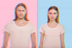 Zeker jong paar die gelijkaardige kleren dragen en zich tegen de kleurrijke achtergrond bevinden royalty-vrije stock foto