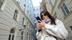 Zeker mooi vrouw het typen bericht die smartphone gebruiken bij historische de bouwachtergrond stock video