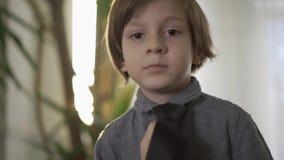 Zeker portret leuk weinig ernstige jongen die op zijn hals lange avondkleding zetten die zich voor het venster met a bevinden stock videobeelden