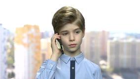 Zeker preteen jongen het spreken op celtelefoon stock videobeelden