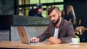 Zeker succesvol bedrijfsmannetje die scherm die van smartphone bekijken laptop het typen tekst het gebruiken stock footage