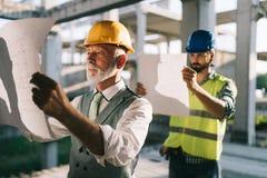 Zeker team van architecten en ingenieurs die aan bouwwerf samenwerken stock fotografie