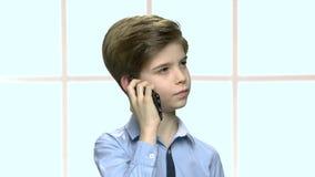 Zeker weinig jongen die op celtelefoon spreken stock footage