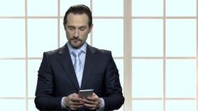 Zeker zakenman het typen bericht op zijn smartphone stock footage