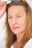 Zekere aantrekkelijke Rijpe Vrouwenglazen stock fotografie