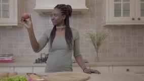 Zekere Afrikaanse Amerikaanse jonge glimlachende vrouw die pastei voorbereiden en op de appel met glimlach kijken stock video