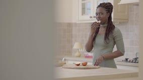 Zekere Afrikaanse Amerikaanse jonge het glimlachen vrouwen scherpe appel voor pastei en het bijten van het met glimlach stock videobeelden