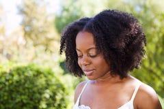Zekere Afrikaanse Amerikaanse vrouw buiten in een tuin royalty-vrije stock foto's
