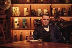 Zekere aristocratische mens met glas van drank in heren` s club stock foto
