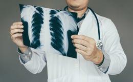 Zekere artsenmens die x-ray film in laboratoriumruimte houden Stock Foto's
