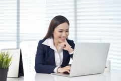 Zekere Aziatische onderneemsterzitting door bureau met binnen weg laptop stock afbeelding