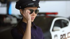 Zekere Aziatische op zonnebril zetten en politievrouw die, moed glimlachen stock video