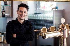 Zekere barkeeper die zich bij barteller bevinden royalty-vrije stock foto's