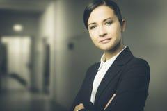 Zekere bedrijfsvrouw die met gekruiste wapens glimlachen Stock Afbeelding