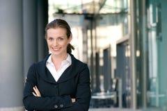Zekere bedrijfsvrouw die met gekruiste wapens glimlachen Stock Foto