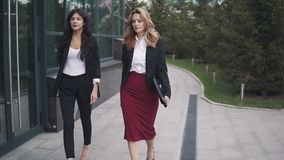 Zekere bedrijfsvrouwen die onderaan de straat lopen Langzame Motie stock footage
