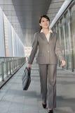 Zekere bedrijfsvrouwenholding aktentas en het lopen Stock Afbeeldingen