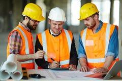 Zekere Bouw Team Checking Plans op Plaats stock afbeelding