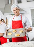 Zekere Chef-kok Holding Pizzas On Tray In Kitchen Stock Foto's