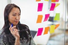 Zekere creatieve onderneemster die multi gekleurde kleverige nota's bekijken Stock Foto