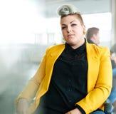 Zekere en gespannen vrouwelijke ontwerper die aan een digitale tablet in rode creatieve bureauruimte werken Stock Fotografie