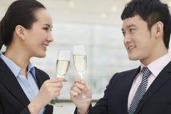 Zekere en succesvolle jonge bedrijfsmensen die met champagnefluiten roosteren Stock Foto's