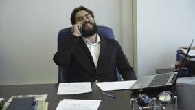 Zekere en succesvolle zakenman die op telefoon spreken en op een stoel zitten Bedrijfs onderhandelingen stock video